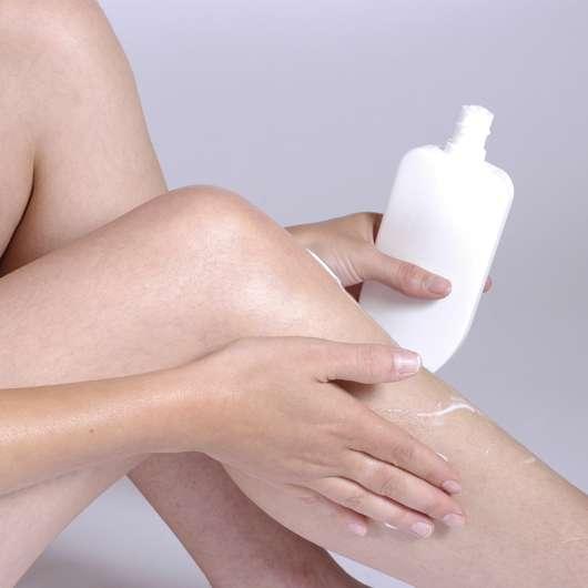 Frau, die sich ihre Beine eincremt