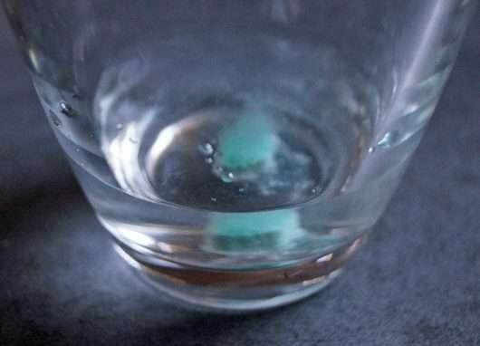 LUSH Crème De Menthe Mouthwash Tab in einem Glas mit Wasser aufgelöst