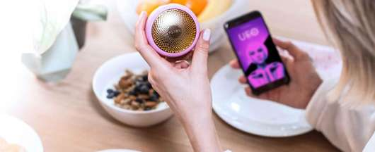 Frau hält FOREO UFO und ein Handy mit der FOREO App in der Hand