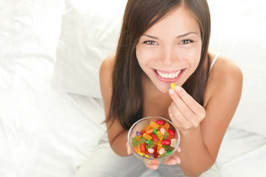junge Frau, die Gummibärchen isst - ©iStock.com/ariwasabi
