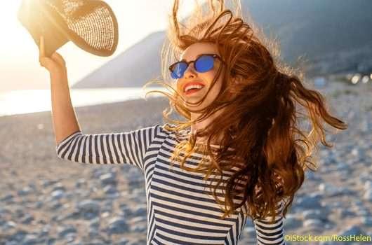 Frau am Strand mit wehenden Haaren und Sonnenhut