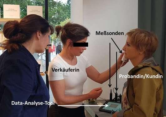 Kosmetikerin führt bei Kundin Hautmessung durch
