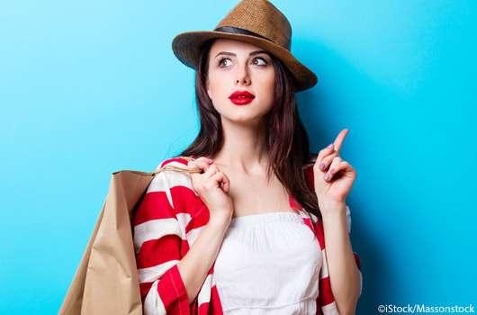 Junge Frau, die shoppen war und eine Tüte über der Schulter trägt